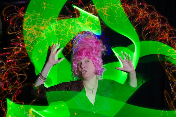 A women in a tall pink wig surrounded by a green swirl of light