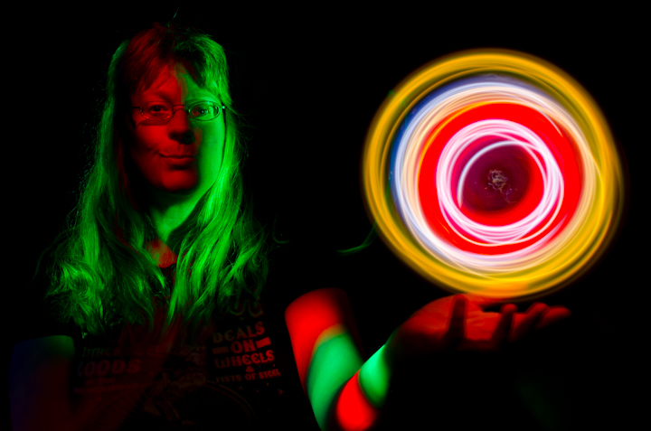 A woman painted with colored lights holding a swirling orb