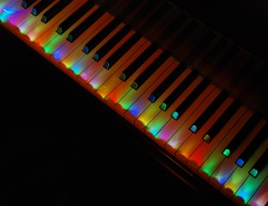 A piano keyboard painted with different colored lights